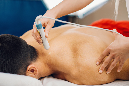 Laser treatment in physical therapy. Therapist using low intensi